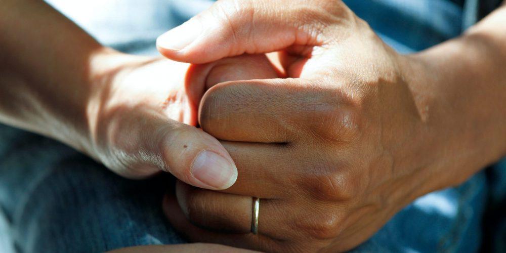 visual of eldery hands being held
